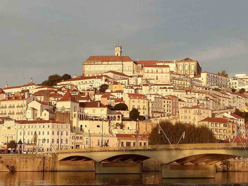 Historic buildings with red roofs overlook the waterfront in the city of Coimbria Portugal.