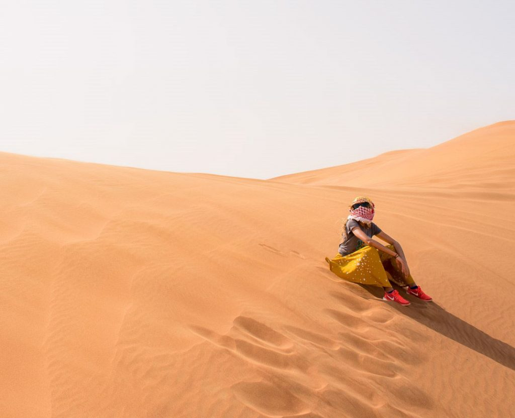 Person sits in the desert at Dubai, UAE, a country that is made up of over 88% expats.