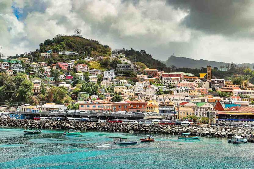 Colorful houses on the hillside in Granada overlooking an aqua harbor with boats - best Caribbean long-stay vacation spot