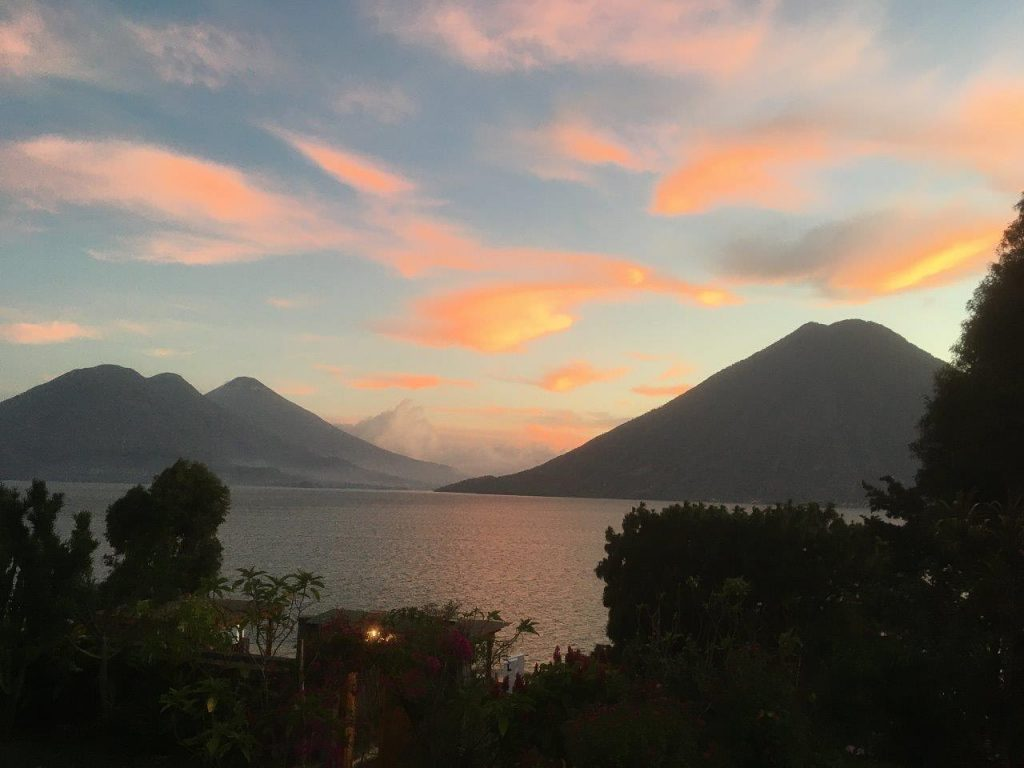 Beautiful Lake Atitlan at dusk, surrounded by the silhouettes of three volcanos and pastel clouds. (best places for American expats)