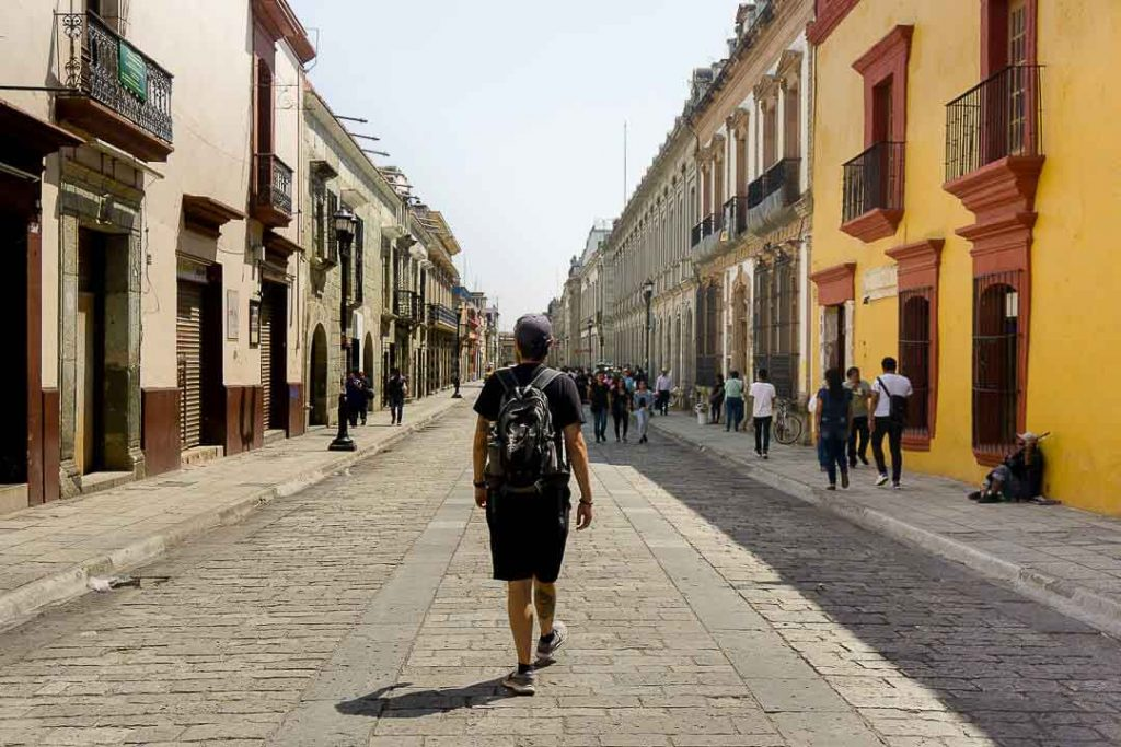 A man with backpack and cap walks in the streets of Oaxaca Mexico. (best places for American expats)