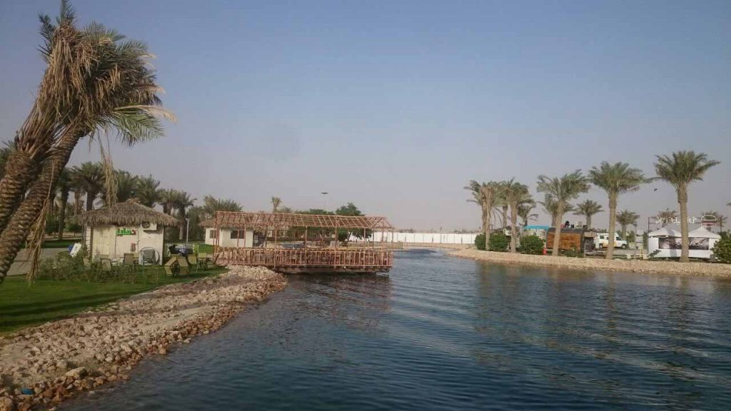 A river with settlements and palm trees in Saudi Arabia.