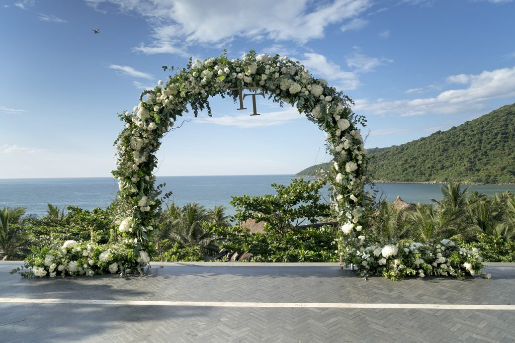 wedding arch of greens and white flowers overlooking the water