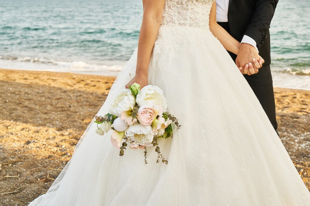 wedding at the beach, bride and groom hold hands