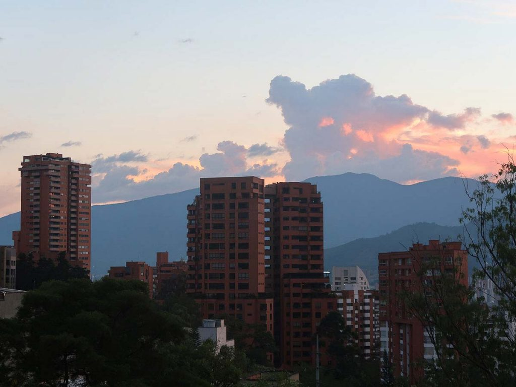 City buildings in Madellin Columbia against a mountain backdrop with colorful clouds (best places for American expats)