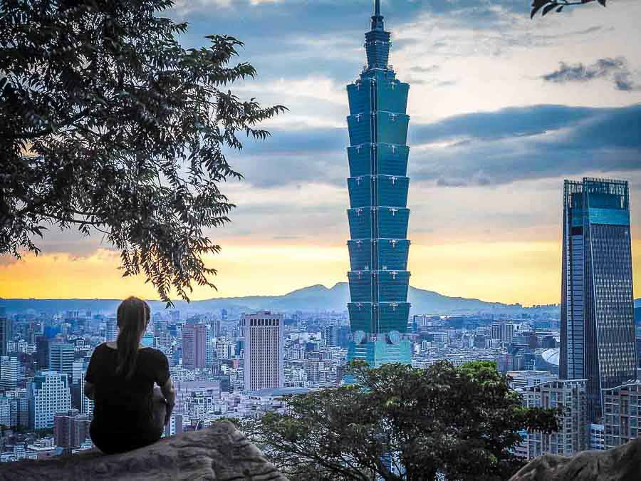 Woman with ponytail overlooks the city of Tai Pai Taiwan at sunrise.