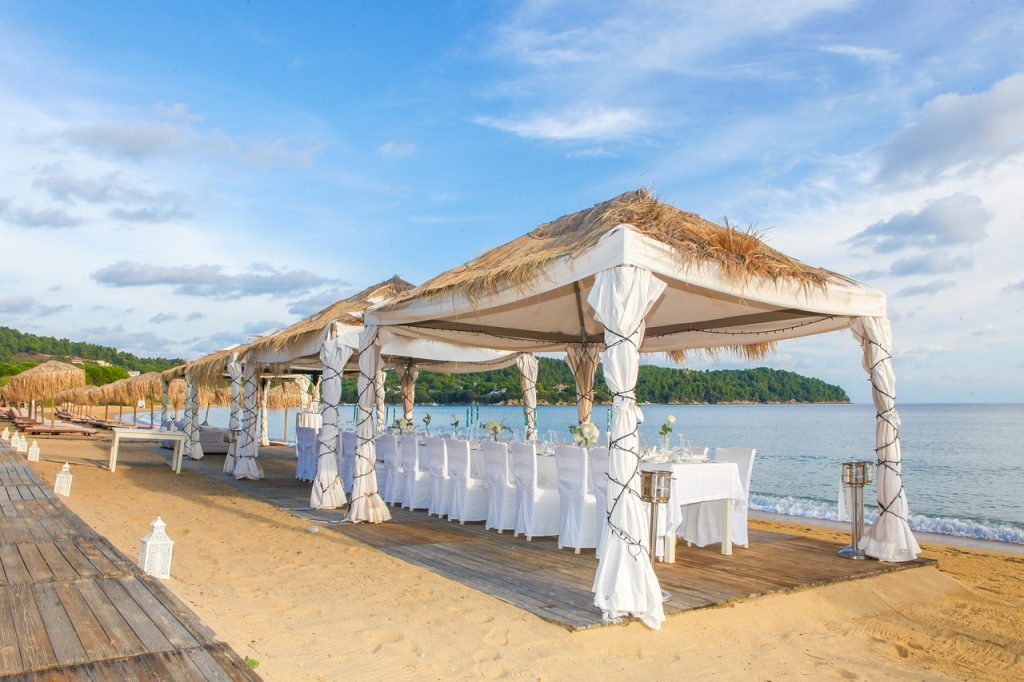 grass tents cover dining tables for a wedding at the beach
