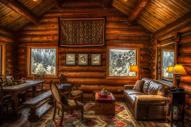 A cozy log cabin with a comfortable seating area, picnic table, and windows overlooking the snowy mountainside.