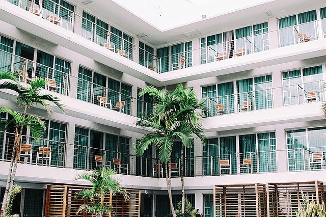 A large hotel resort with glass doors and balconies overlooking palm trees.