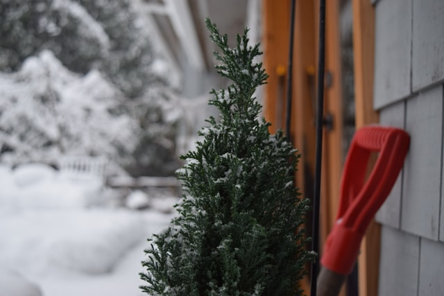 Checklist for Winterizing Your Home: Take inventory of shovels and winter gear (shown: shovel handle, snow, small tree by entrance)