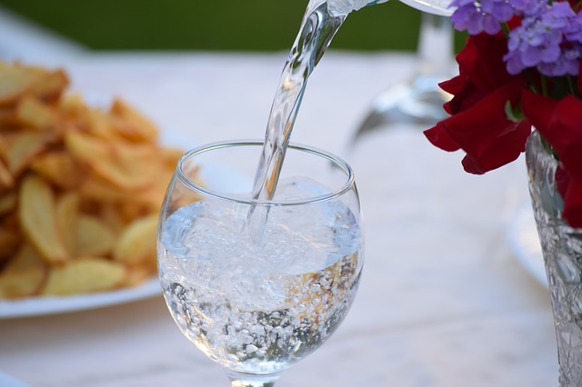 Filling glass with water - stay hydrated for optimum travel and fitness.