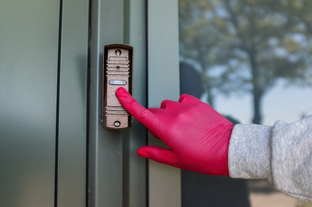 person with red gloves rings doorbell (home security)