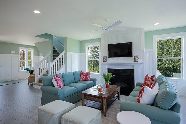Open floor plan living room with teal couches, red pillows, ottomans, and a coffee table arranged in a conversation area before a fireplace.