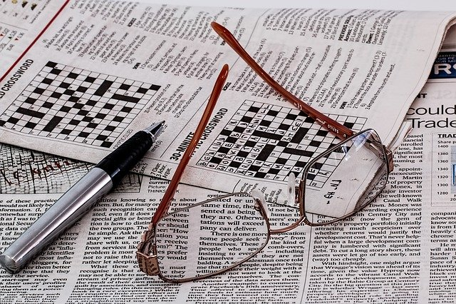 Newspaper with crossword puzzles, eye glasses, and a pen