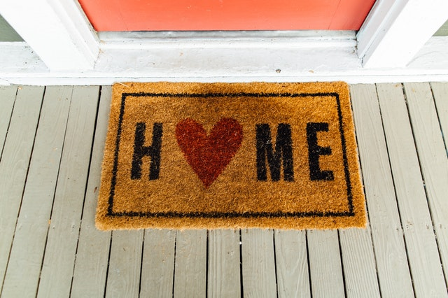 Brown door mat that reads, HOME. Letter O is replaced with a red heart.