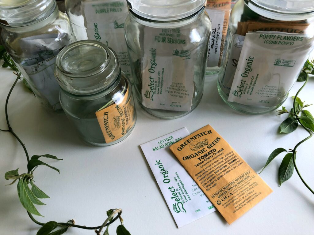 Organic garden seeds stored in envelopes and within glass jars.