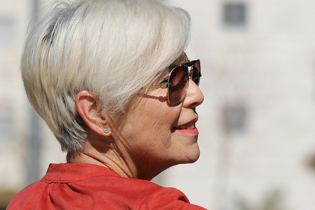 An older women with coral lipstick and sunglasses, smiling