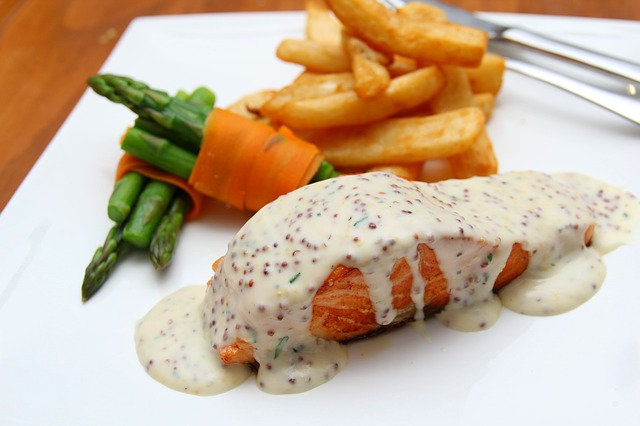 Salmon with a mustard cream sauce, asparagus wrapped with carrot strips, french fries.