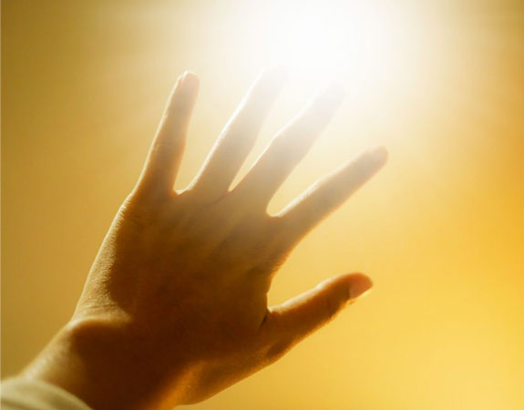 Hand outstretched to block the bright sun