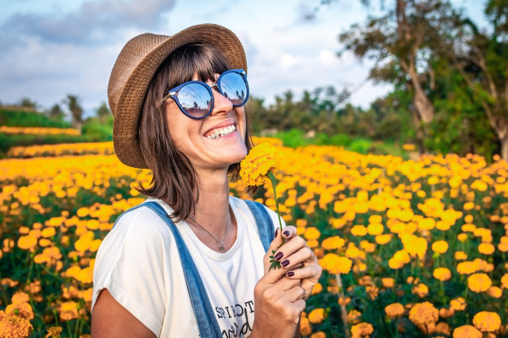 Woman wearing wide-brimmed hat and sunglasses in a sunflower field.