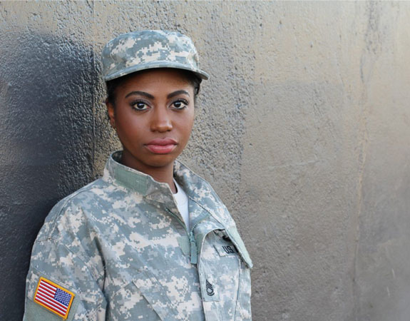Veteran stands against a wall. She may be covered by insurance through the VA