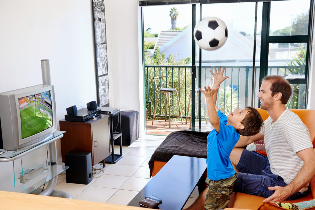 Visually impaired father and son watch the World Cup on their TV
