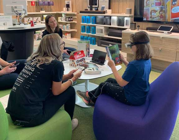Women wearing eSight's low vision technology gives a presentation at work as part a corporate social responsibility partnership with Microsoft Partner