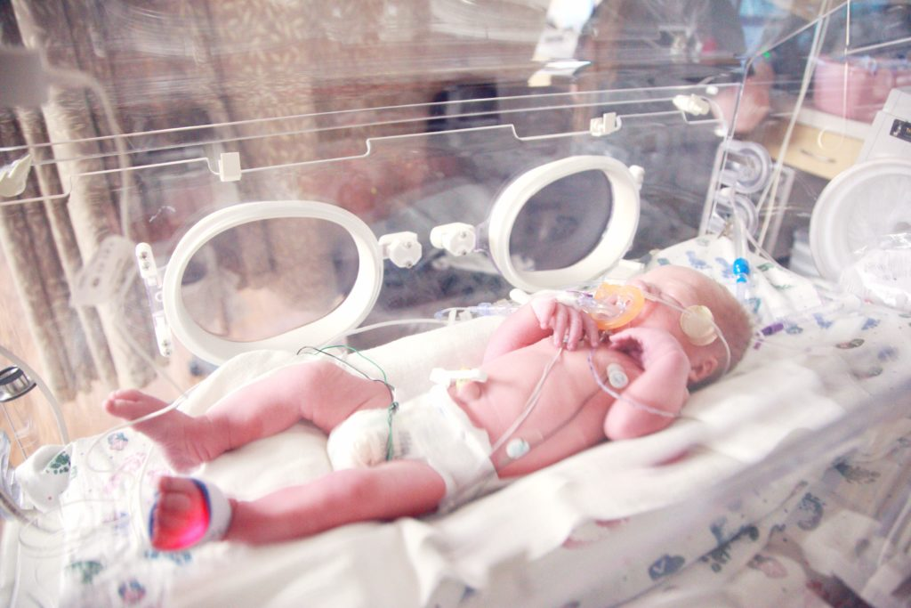 Premature baby in an isolate incubator with oxygen.