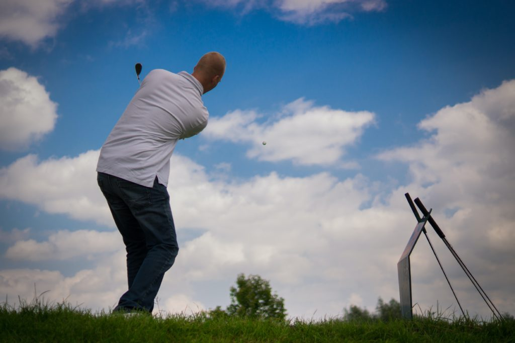 Man hitting golf ball into the air.