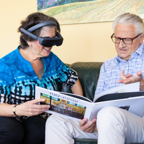 Older couple reading a book wearing eSight's vision-enhancing glasses
