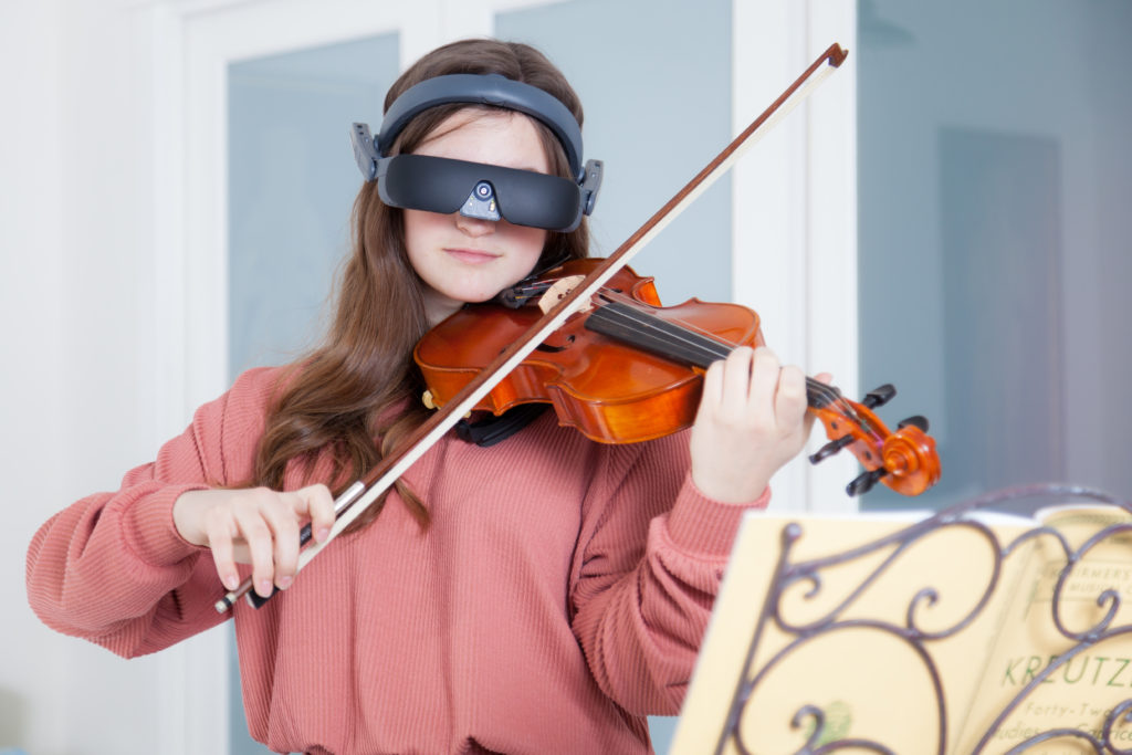 Young woman plays violin using her wireless hands free vision enhancing device