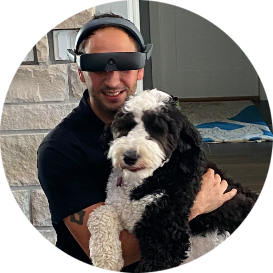 Chris is wearing eSight 4 and photographed with his dog