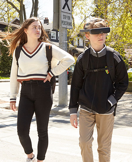 Two teenagers cross the street using eSight's electronic eyewear for the blind