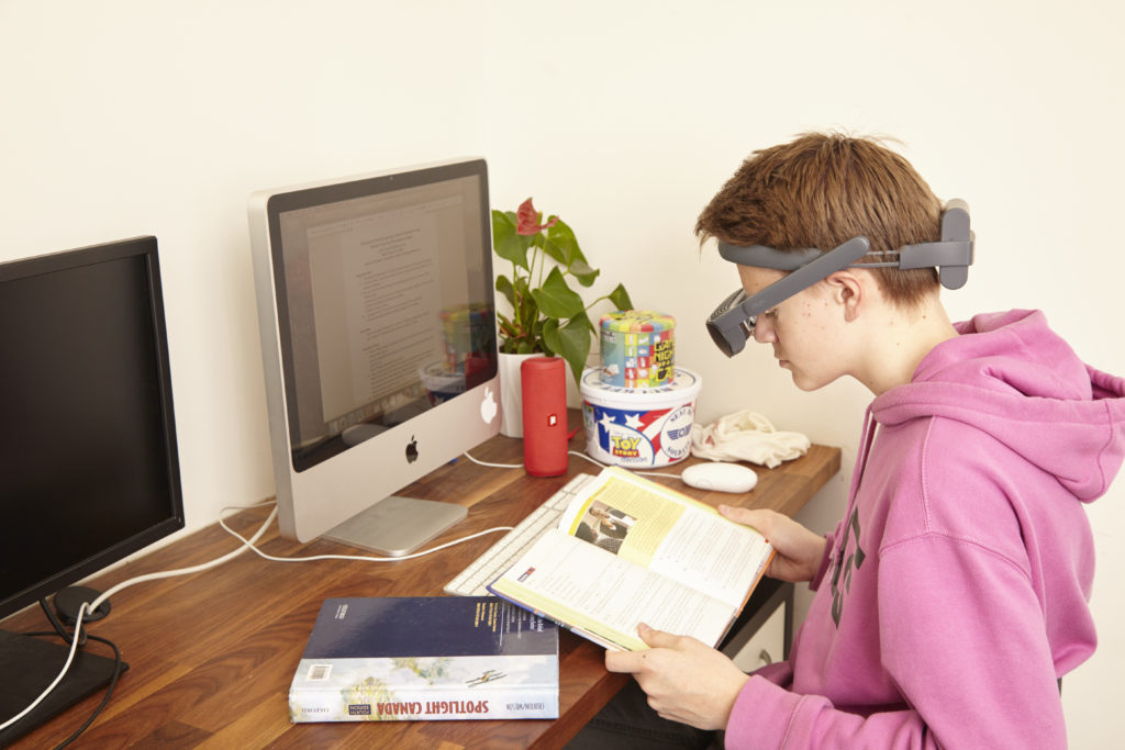 Low vision student using eSight to read his textbook