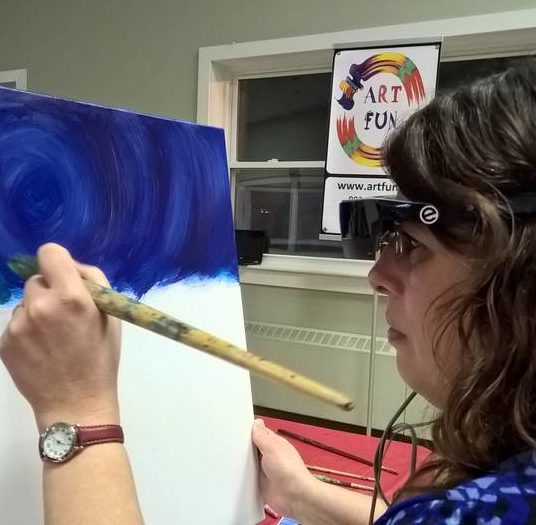 Tammy Martin painting while wearing an eSight