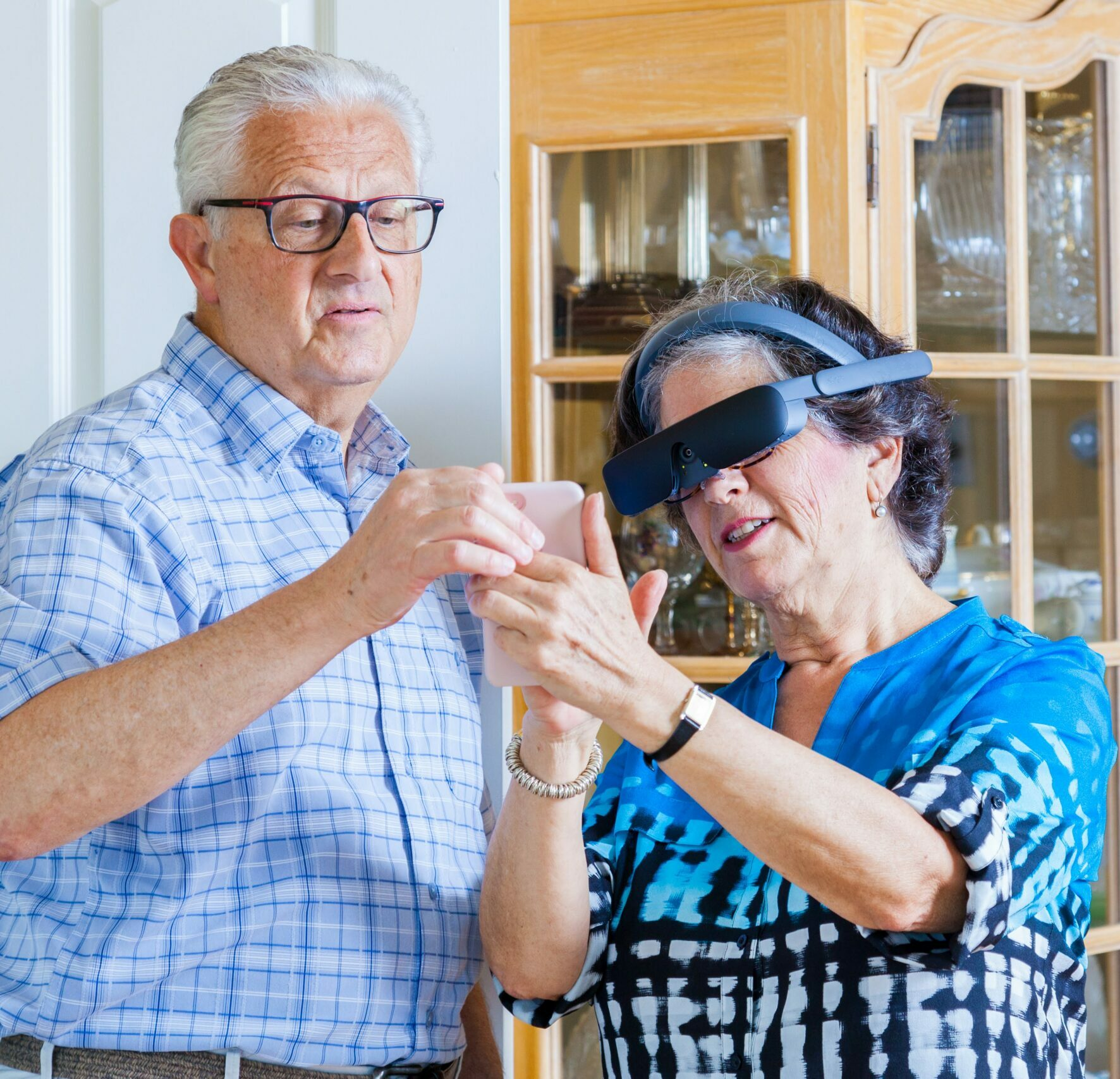 An elderly couple looking at their phone