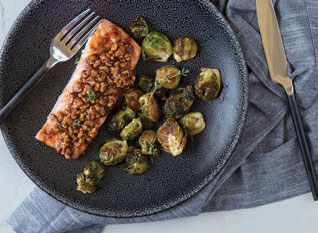 Maple Walnut Crusted Salmon on a plate with roasted Brussels Sprouts