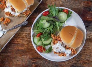 one buffalo chicken sloppy joe on a plate with salad