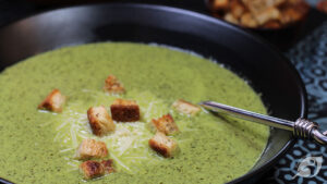 closeup of creamy spinach soup in a black bowl
