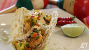 Shrimp Tacos with Mango Salsa on a plate with chilis and lime
