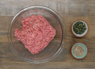 Bowl with 1 pound ground turkey and smaller bowls with chopped sage and rancher steak rub