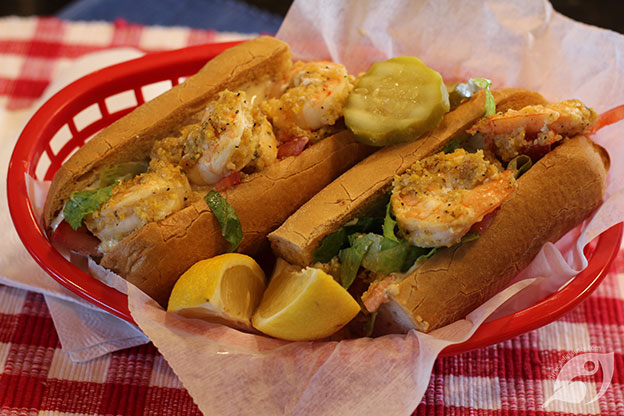 colseuo Buffalo Shrimp Po'Boy two 6-inch halves in a basket with lemon and pickle