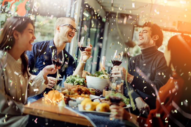 two women and two men at a holiday table enjoying wine and food