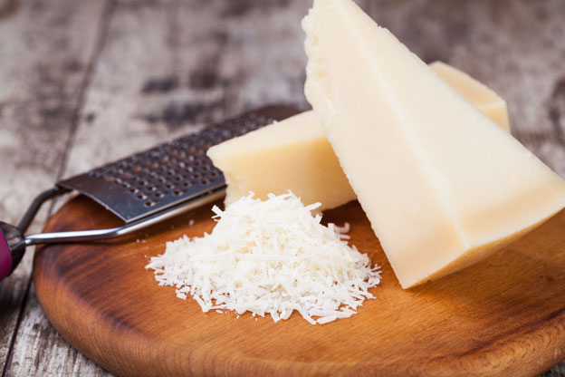 grated parmesan cheese with a microplane grater on a cutting board
