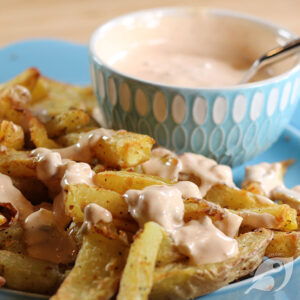 Closeup of fries with a drizzle of our favorite dipping sauce with bowl of sauce in the background.