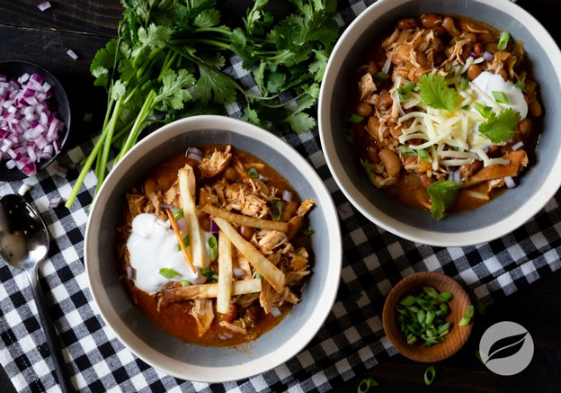 Two BBQ Chicken Chili bowls on a blue check towel with red onions, cilantro and green onions
