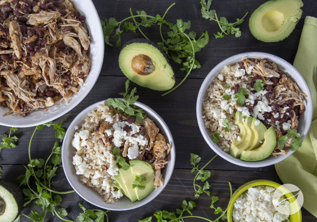 Two Pollo Asada Rice Bowls with shredded chicken in a seperate bowl cheese and avocado on a board