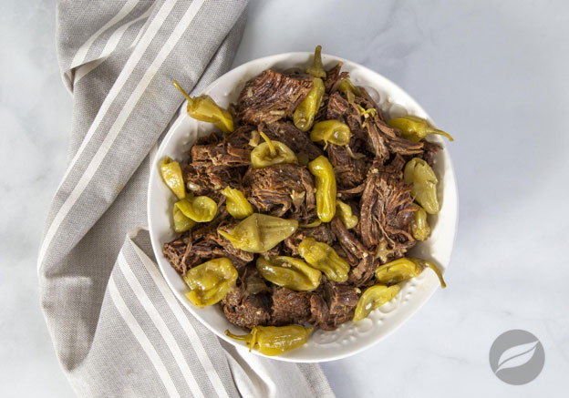 Mississippi Pot Roast in a bowl with a grey striped towel in the background