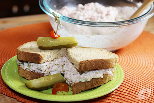 Ham Salad Sandwich on a plate with a pickle and the bowl of the spread in the background.