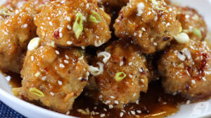 Close-up of Baked Orange Chicken Meatballs on a plate with chopsticks.